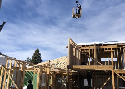 Man hanging from crane during the construction of custom built home in Steamboat Springs