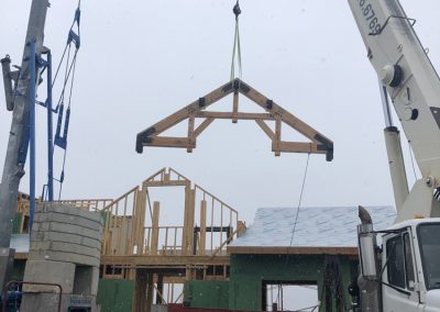 Crane holding a Truss during the construction process of a custom built home in Steamboat Springs