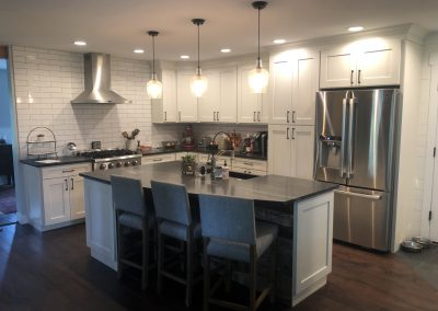 Custom Kitchen with white tiles and cabinets with chrome appliances