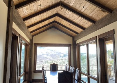 Vaulted ceiling with wood beams over dining room table in custom built home in Steamboat Springs
