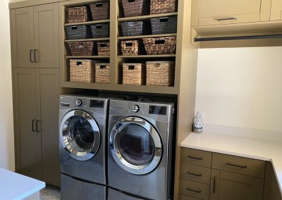 Residential custom built laundry room with built in shelfing.