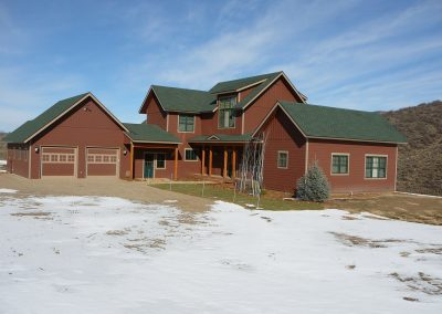 Exterior view of red custom residential home with green roof and double garage in Steamboat during the winter