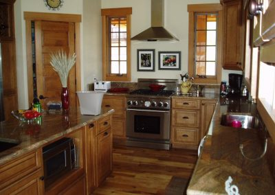 Residential kitchen with custom cabinets and stove with a hood