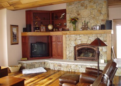Residential living room with entertainment center build in and stone fireplace