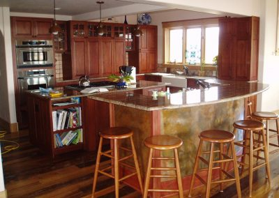 Residential Kitchen with cherry wood cabinets, farm style sink, island with cooking area