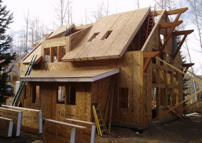 Framing of house during construction surrounded by aspens and pine trees