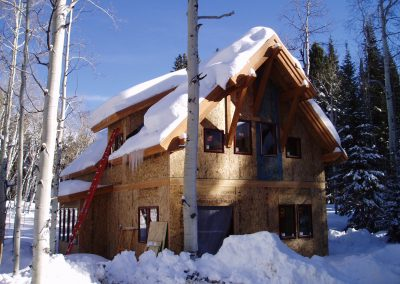 House during construction surrounded by aspens and pine trees covered in several feet of snow