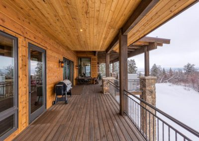 Large deck with smoker overlooking a snow covered field.