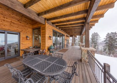 Covered outdoor deck with table and grill.