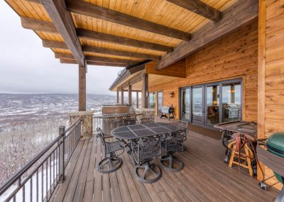 Outdoor covered deck with dining table.